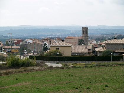 Vista de l'església i de les primeres cases d'Olvan des del camí del Boix