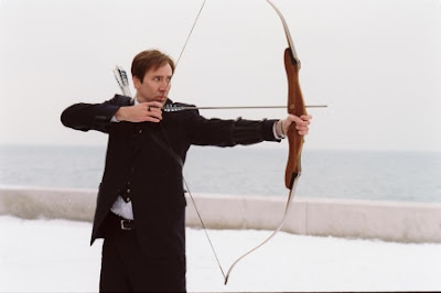 Nick Cage drawing back a bow and arrow in The Weather Man