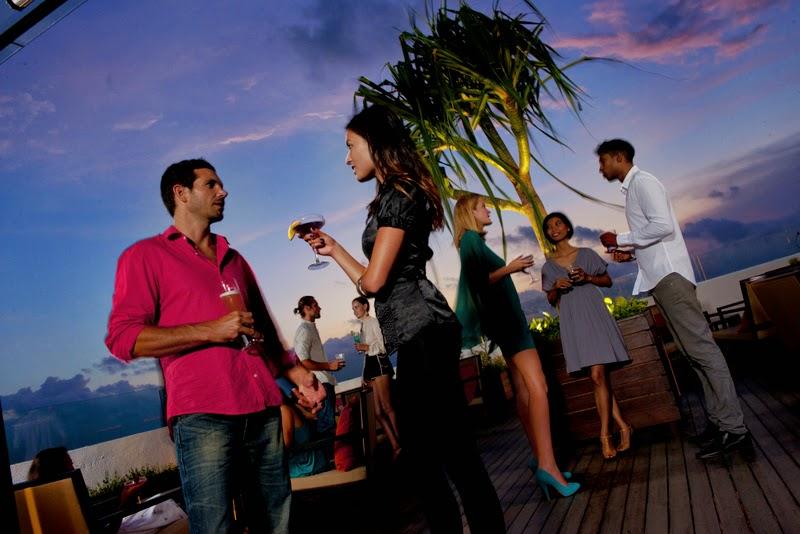 Personas tomando una copa en una terraza en un ambiente relajado