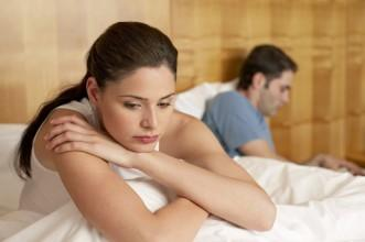 woman-sat-on-a-bed-looking-sad-with-a-man-sat-behind-her - Not Having Sex.... 7 Ways To Start Again