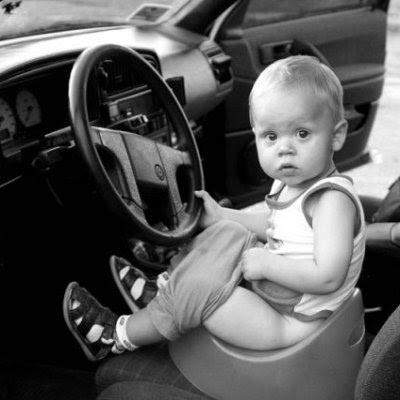 Crianças pequena sentada num troninho colocado no banco do motorista.