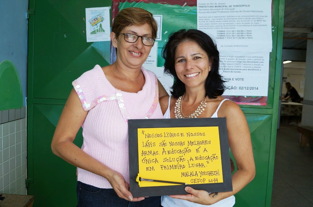 As professoras de artesanato Edna e Liliane mostram a placa entregue a Escola