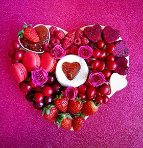 Uma tábua de frutas e doces em formato de coração