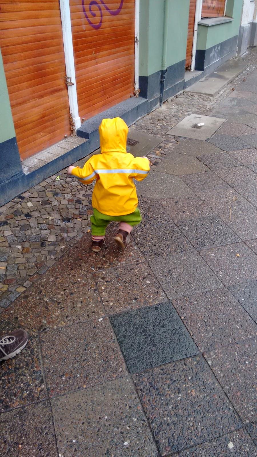 Terrorpüppi in Regensachen auf dem Gehweg