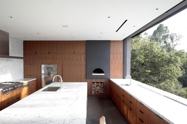large kitchen with wood and stone touch, natural light from large glass