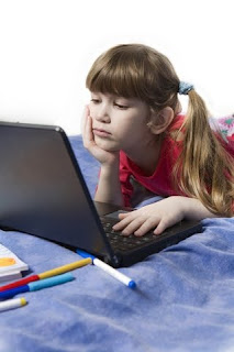 Child on a bed browsing her laptop