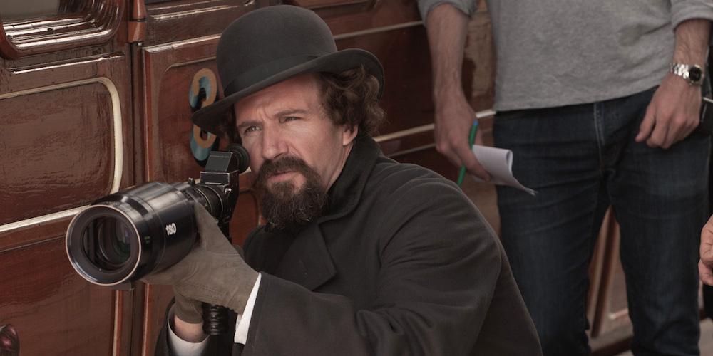 ralph fienes como diretor de cinema operando uma câmera cinematográfica no set do filme o nosso segredo