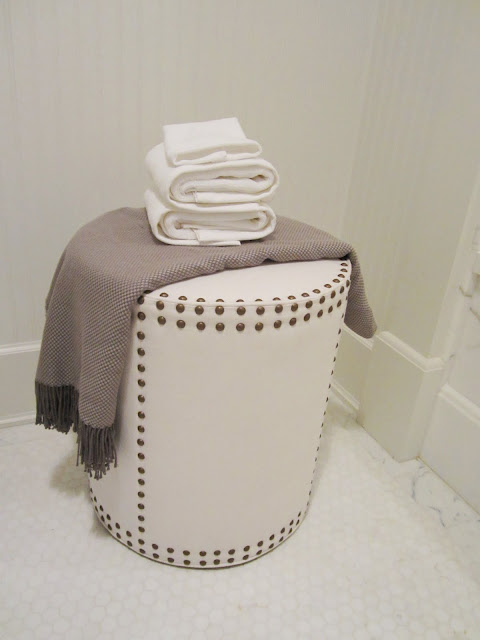 Close up of the little leather stool with nail head trim holding a fringed throw and white towels in a small bathroom and white hexagon tile floor in the House of Windsor