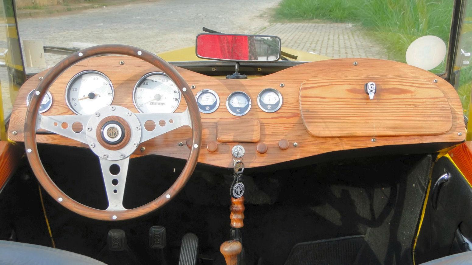 O painel de madeira é personalizado, assim como o volante de três raios, de uma elegância e esportividade impecável.