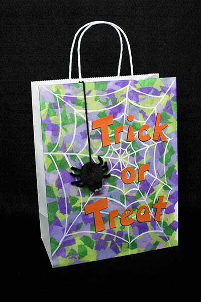 Trick or treat bag made with shades of purple and green tissue paper with cute black spider on a white web with large orange letters spelling trick or treat