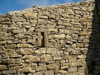Detall d'un dels murs amb finestra, tot fet amb la tècnica de la pedra seca