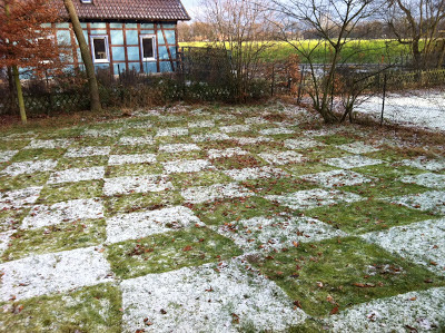 Backyard chequerboard created by melting snow squares on the grass.
