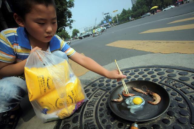 Hình ảnh được chụp vào hôm thứ tư, 31/7 vừa qua cho thấy một chú bé đang chiên một quả trứng và những con tôm trong chiếc chảo được đặt trên một miệng cống vào một ngày hè nóng nực ở Tế Nam, tỉnh Sơn Đông, miền đông Trung Quốc. Ảnh : AP Photo/China Out.