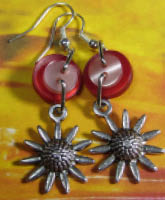 Flower charm fun earrings have silver sunflower charms hanging from layered red and pink buttons