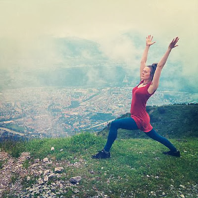 Girl in a yoga pose with mountain scenery background