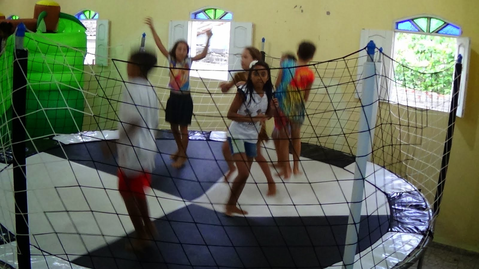 AS CRIANÇAS FELIZES BRINCANDO NO PULA-PULA