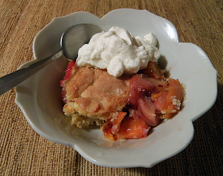Dish of Peach Cobbler with Whipped Cream and Spoon