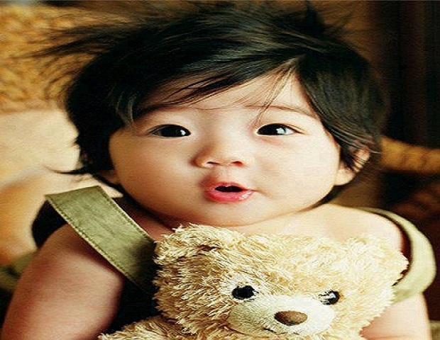 un magnifique bébé asiatique avec son peluche