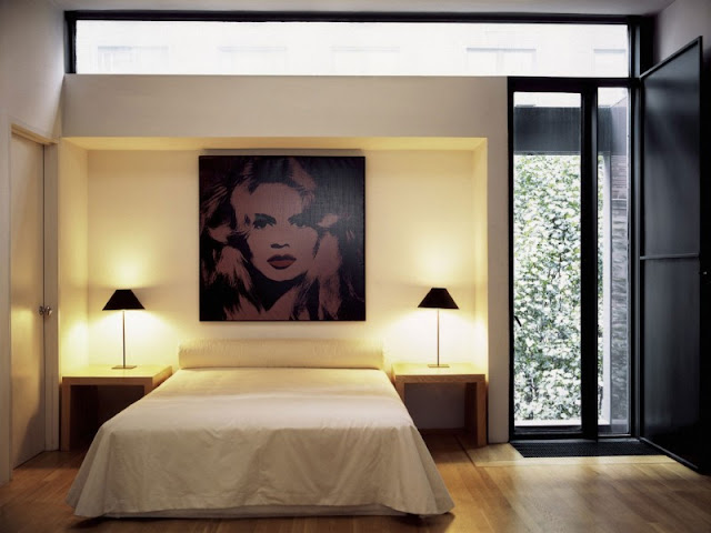 Photo of second modern designed bedroom with minimalist bed and painting on he wall