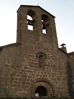 La façana de ponent amb la porta d'entrada i el campanar d'espadanya