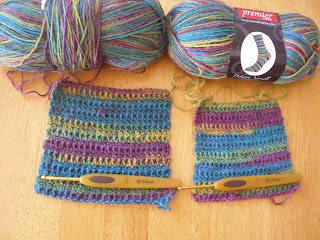 two swatches laying side by side, with the corresponding ball of yarn above each swatch