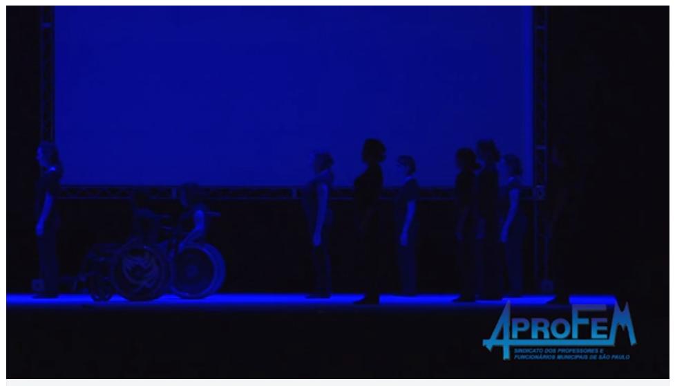 Descrição da Foto: Intérpretes estão de pé, entre eles dois cadeirantes. Estão virados para a lateral esquerda sobre luz azul.