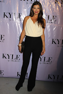 Ali Landry wearing black pants and a white top