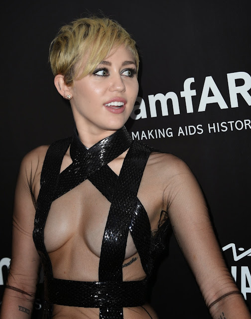 Mileey Cyrus Goes Topless Covering her nipples with a Stripe at amfAR LA Inspiration 2014 GALA