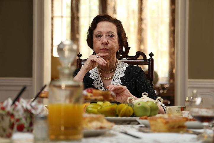 Cena do filme infância de Domingos oliveira onde a personagem de fernanda montenegro está sentada à mesa tomando café da manhã