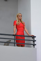 Paris Hilton in a bright orange dress on a hotel balcony