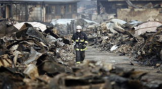 A rescue worker walks through the rubble in a devastated Japanese town.