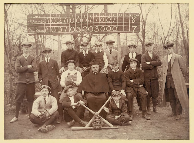 Baseball team, Eymard Seminary, Suffern, N.Y. Photograph shows the Eymard Seminary (of Suffern, N.Y.) baseball team gathered around a clergyman wearing cape and biretta, all posed beneath a scoreboard showing that the Eymard team scored a run in the top of the twelfth inning to beat the Don Bosco team by a score of 8 to 7.