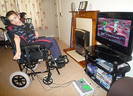 Photo of Colin posing with his C-SID accessible controller set-up playing Zelda on his GameCube.