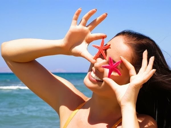 Woman holding starfish up to her eyes