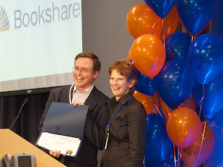 Two people at podium, smiling and holding up a certificate