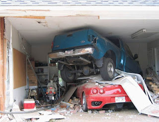 Crashed pickup truck perched atop a sports car in a garage