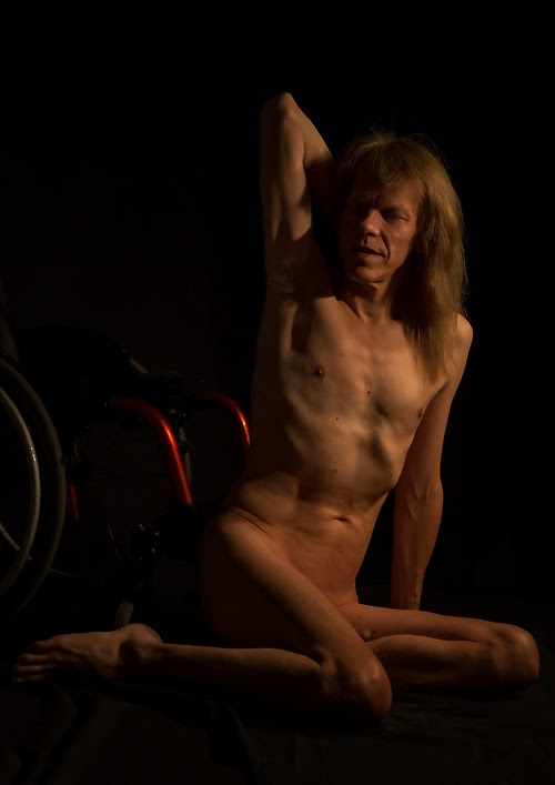 Photo of naked man with long blonde hair, posted sitting on the floor in front of a partially visible wheelchair