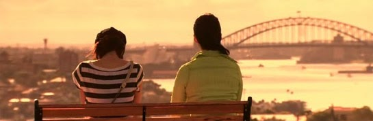 Misaki and Mikami sit on a bench with a view of the Sydney Harbor Bridge.