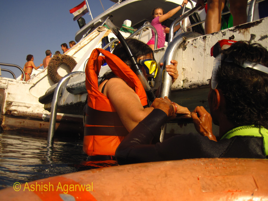 Tourist wearing snorkeling equipment getting down from a ship in the Red Sea