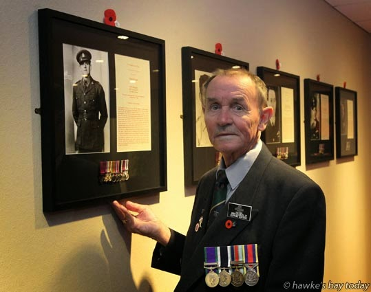 John Stables, support adviser, Hastings RSA, Hastings, pictured with a portrait of Keith Elliott VC (Hawke's Bay) in the new Victoria Cross Room, which was officially opened on Anzac Day. photograph