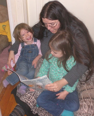 Mom reading to preschool aged girls.