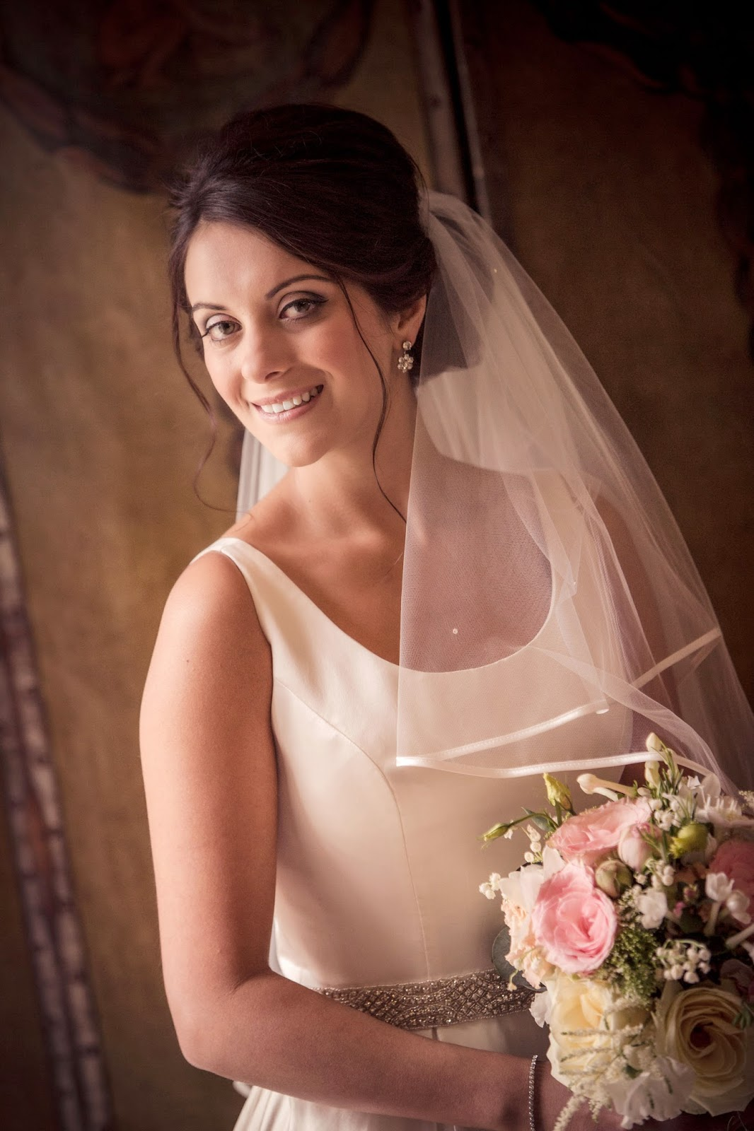 Bride Gemma poses for a picture before the ceremony. A textured bun with soft volume is the perfect style for a full veil