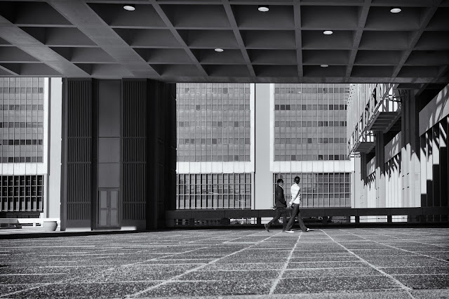 A man and a woman walk against a backdrop of architecture