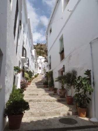 Urlaub mit Baby. Blick auf eine Gasse der weißen Stadt Frigiliana mit Treppen.