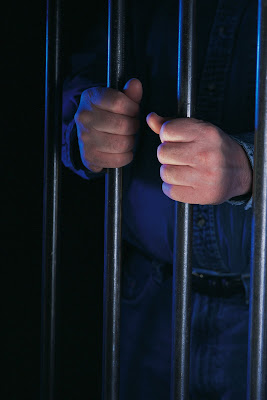 Image of inmates hands on jail bars.