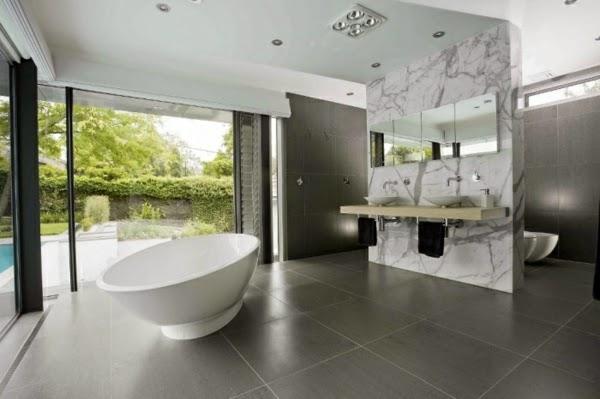 Baños Grises Modernos:Un baño muy espacioso donde el color gris ocupa la pared y el suelo