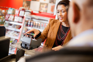 Pic of woman using contactless payment in shop with shopkeeper