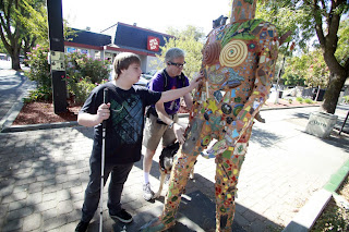 Michael May, right, CEO of Sendero Group, and William Jeffries of Roseville reach the a statue at Fourth and G streets Saturday morning on a scavenger hunt in downtown Davis. Image copyright Davis Enterprise.