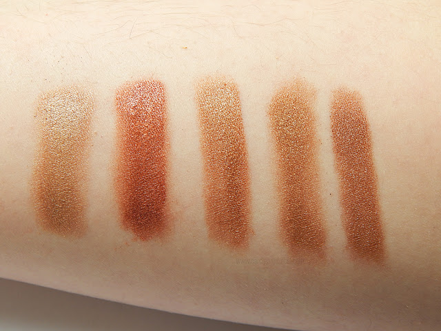Gold and orange eyeshadow swatched on someone's arm