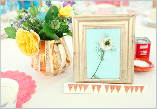 picture frame as table name with flowers in a vintage teapot